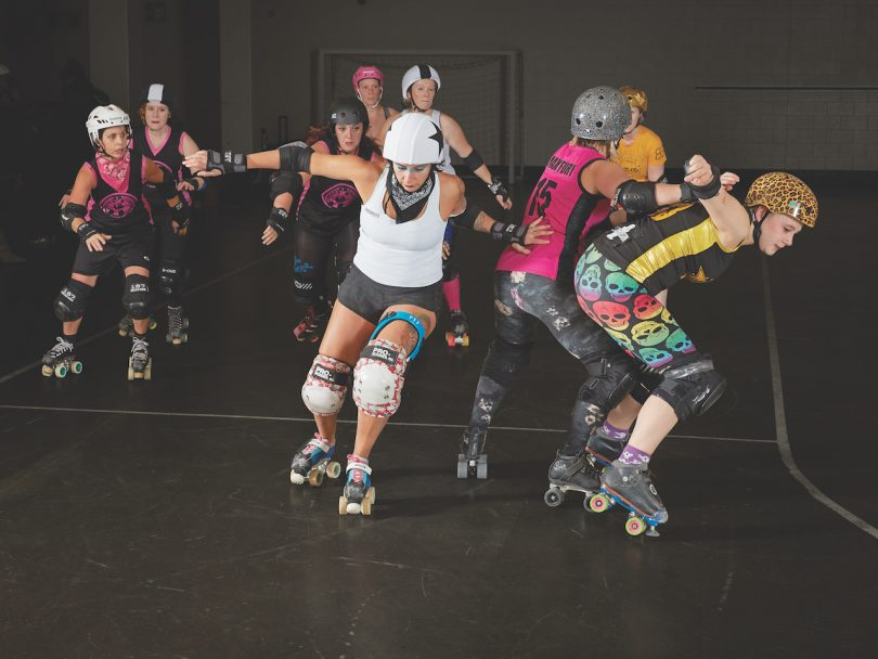 A group of women roller-skating at roller derby to illustrate a piece on women and contact sports