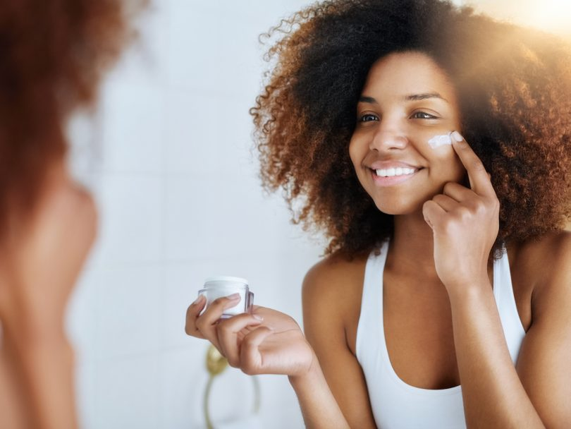 A woman applies moisturizer. How many skincare products do you really need? Do you actually need a serum?
