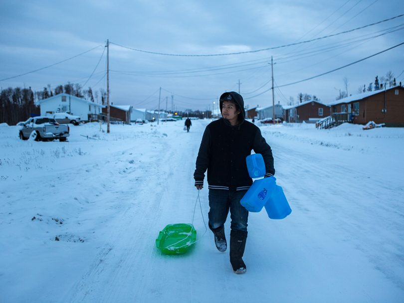 tap water Neskantaga First Nation-a man walks down a snowy road carrying empty water jugs