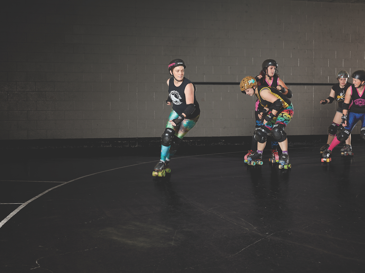 A group of women are roller-skating. Roller derby is very physically intense, with free rein to knock people down