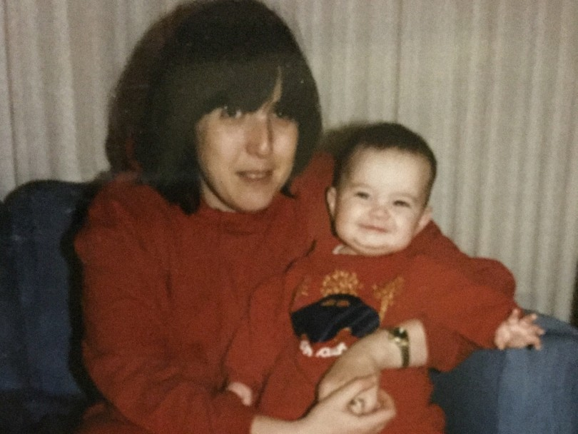 grief- a mom holding her baby wearing matching red sweat suits