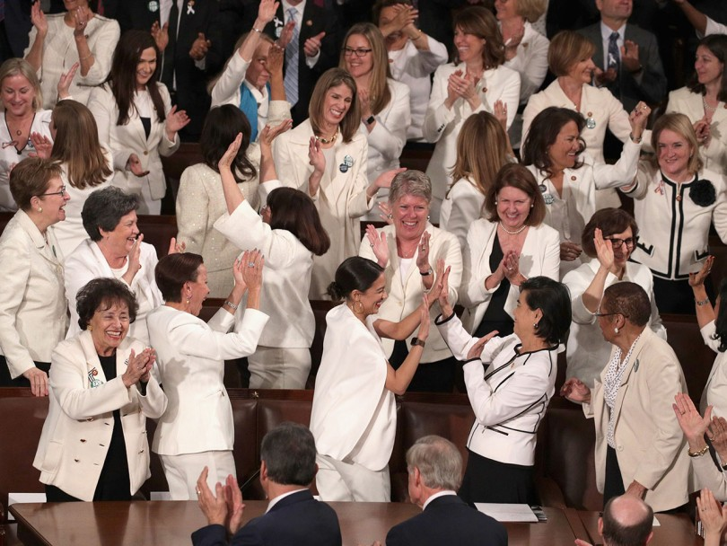 SOTU white suits explained: Group of Democratic women wearing white celebrate and clap