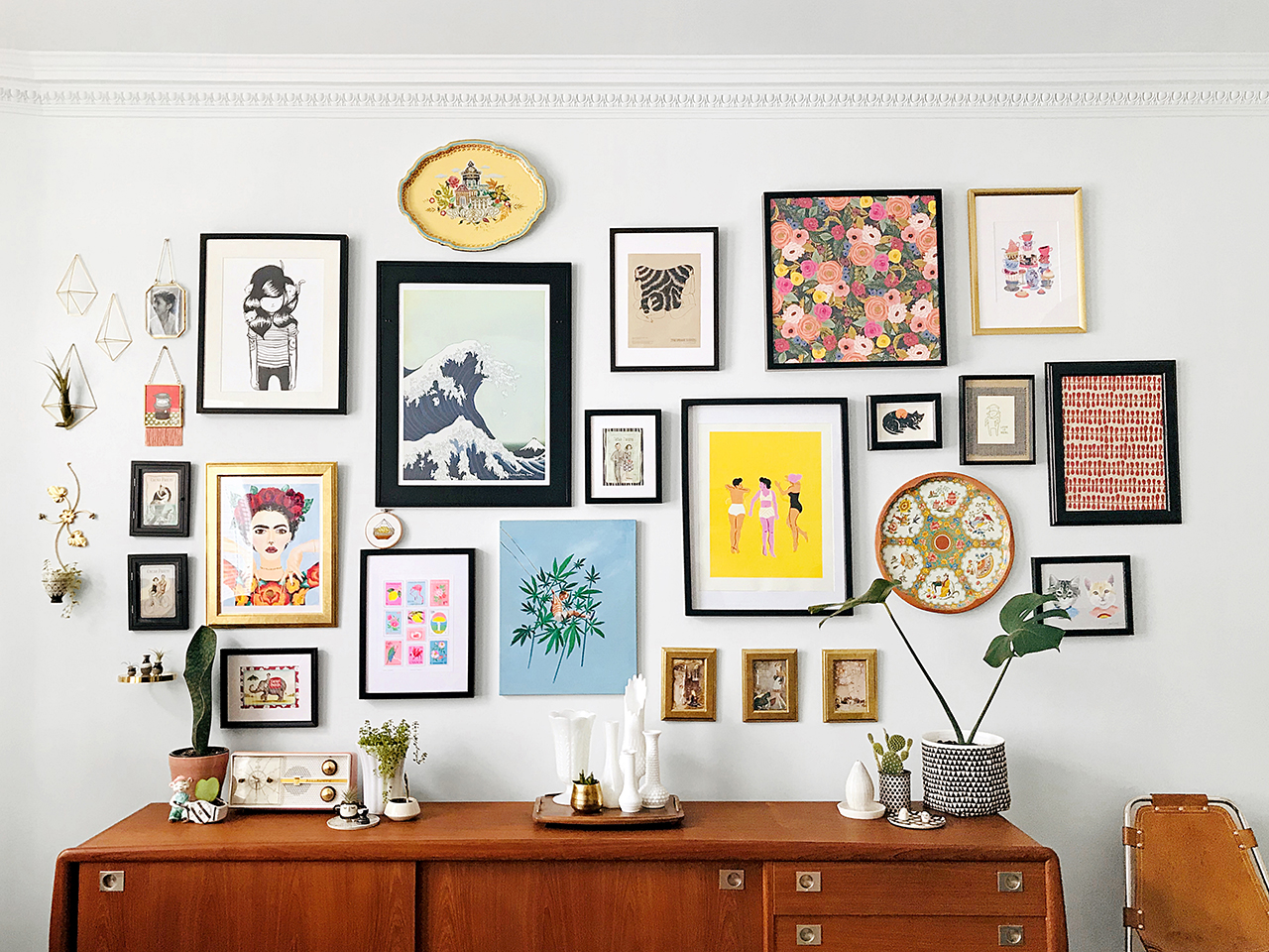gallery wall- an assortment of art and objects hang on a wall above a sideboard