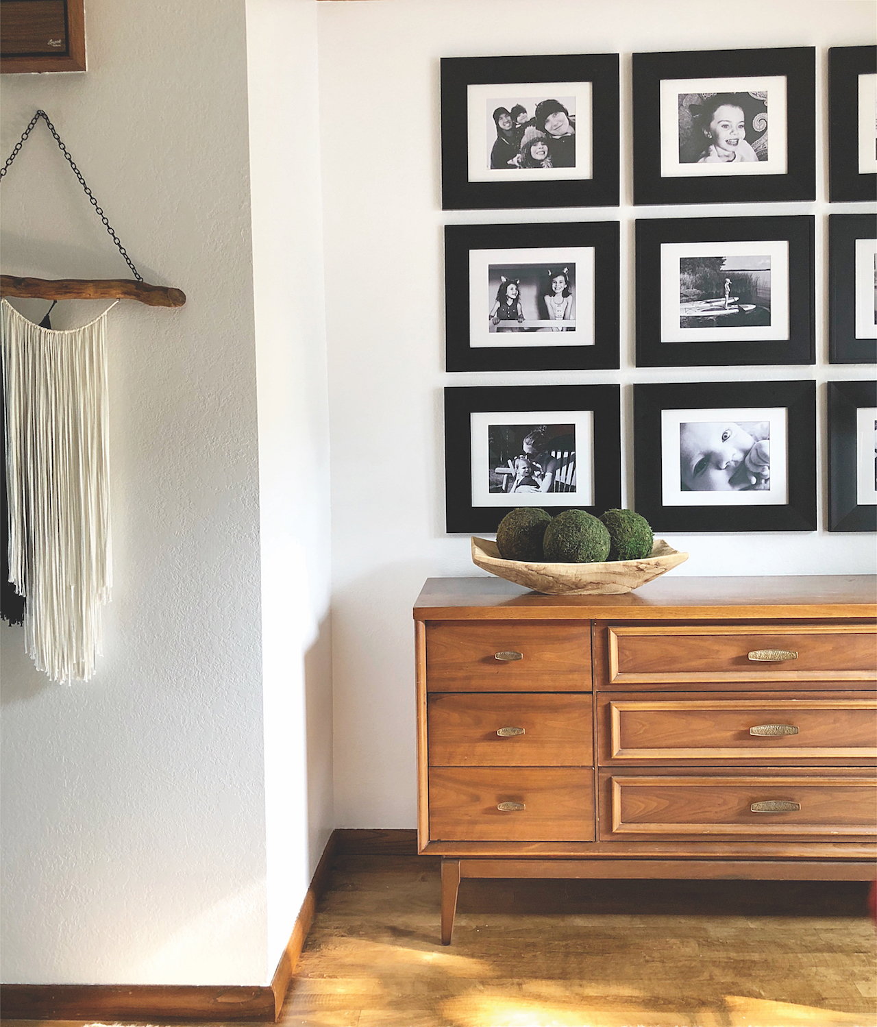 gallery wall-neatly ordered black frames fill a wall above a sideboard