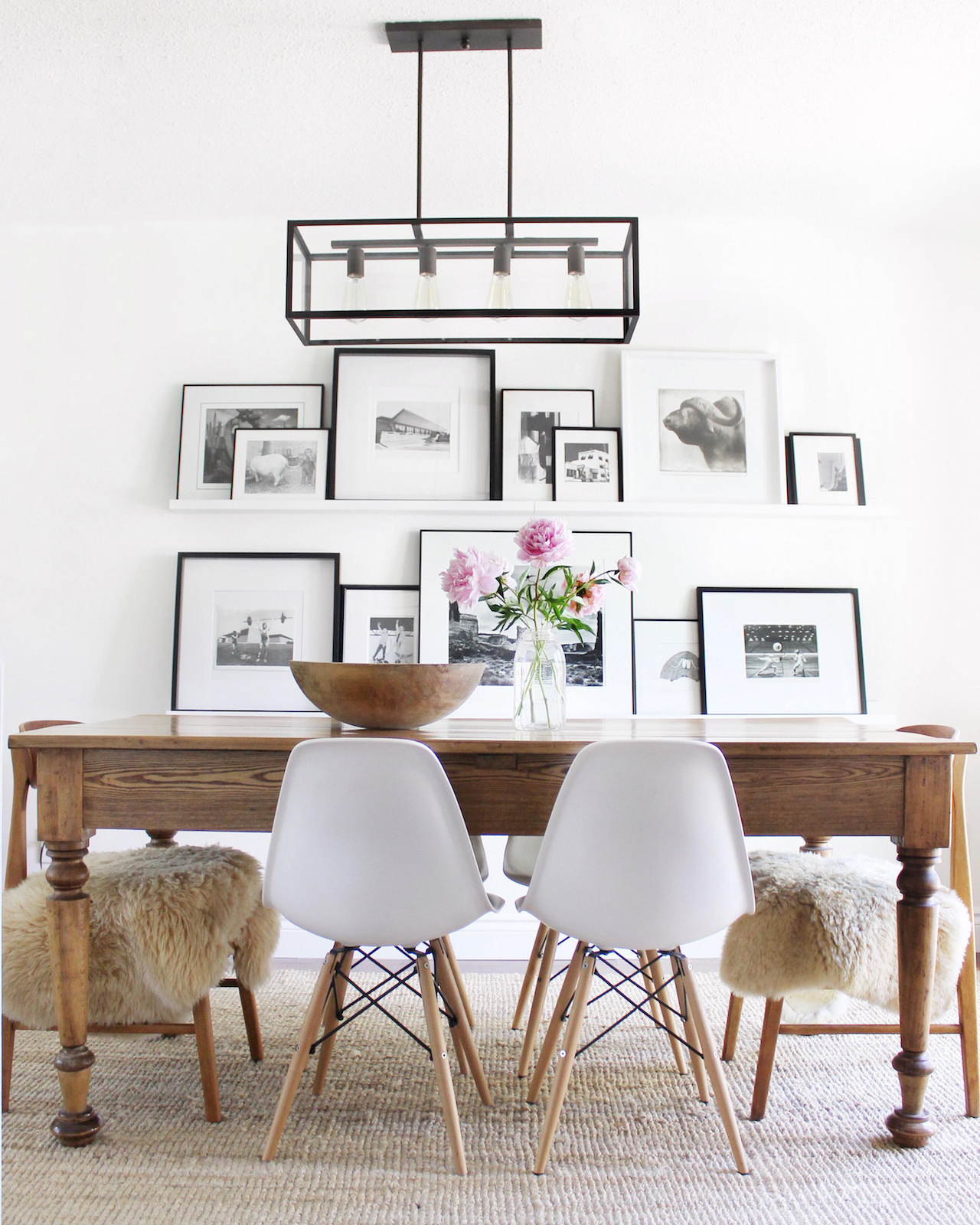 gallery wall-dining room ledge displays various kinds of framed artwork