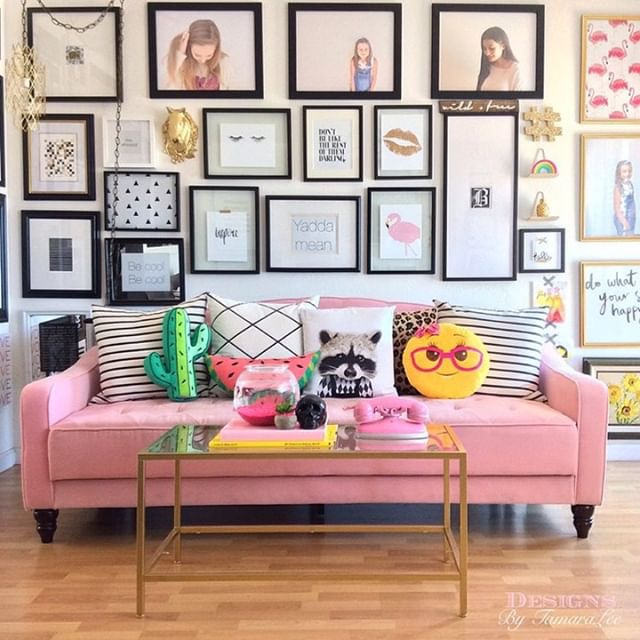 gallery walls-bright and bold display of framed artwork behind a pink couch