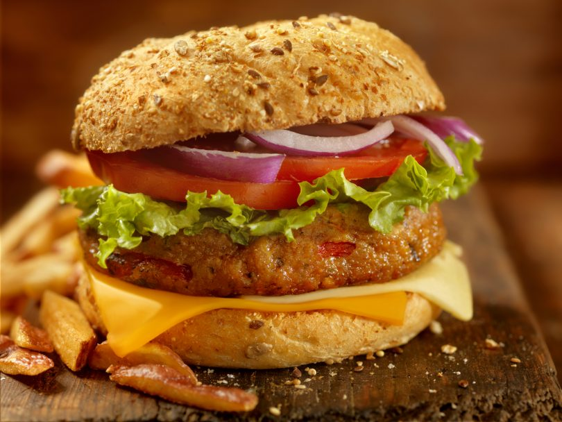 ultra-processed foods-veggie burger on a bun with onion, tomato, lettuce and cheese.