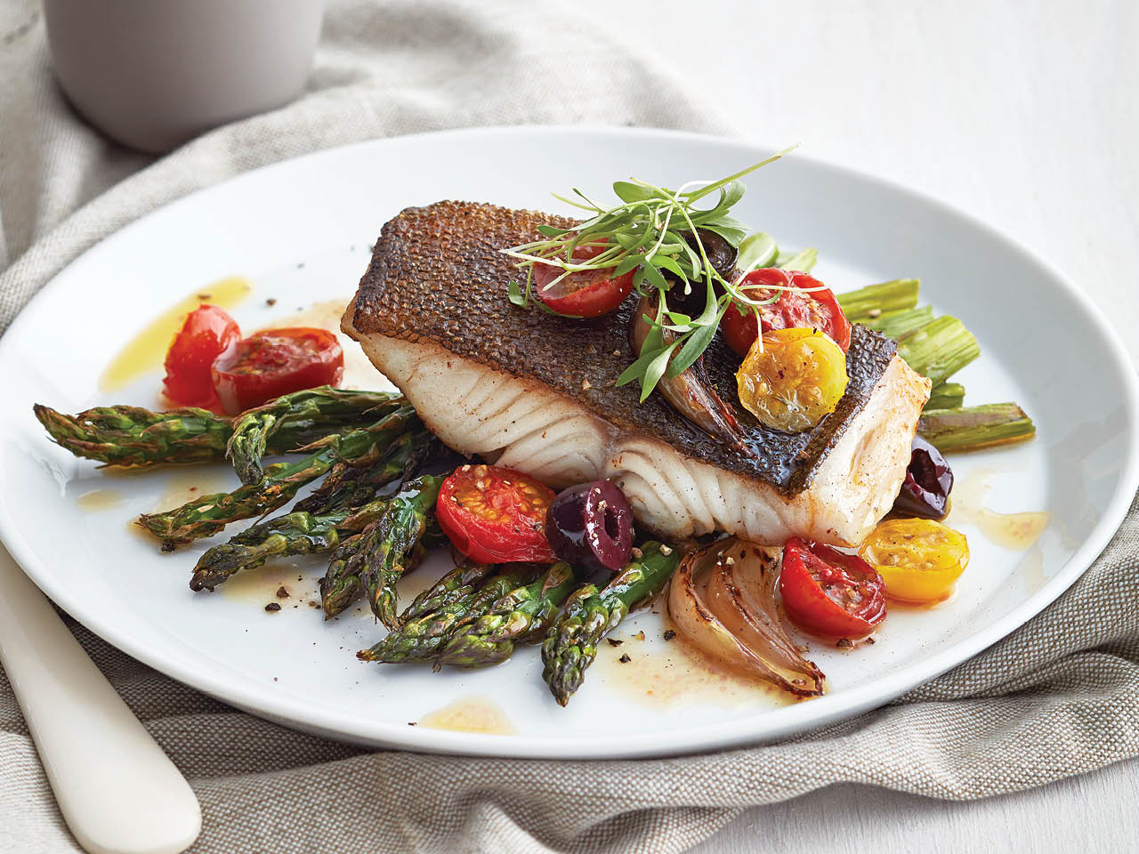 Roasted black cod with tomatoes and asparagus on white plate