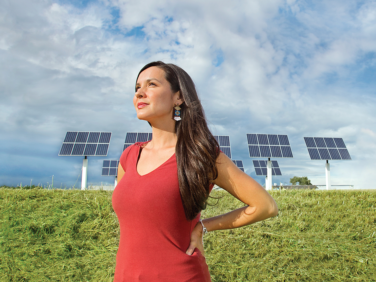 Entrepreneur Melina Laboucan-Massimo stands in front of outdoor solar panels