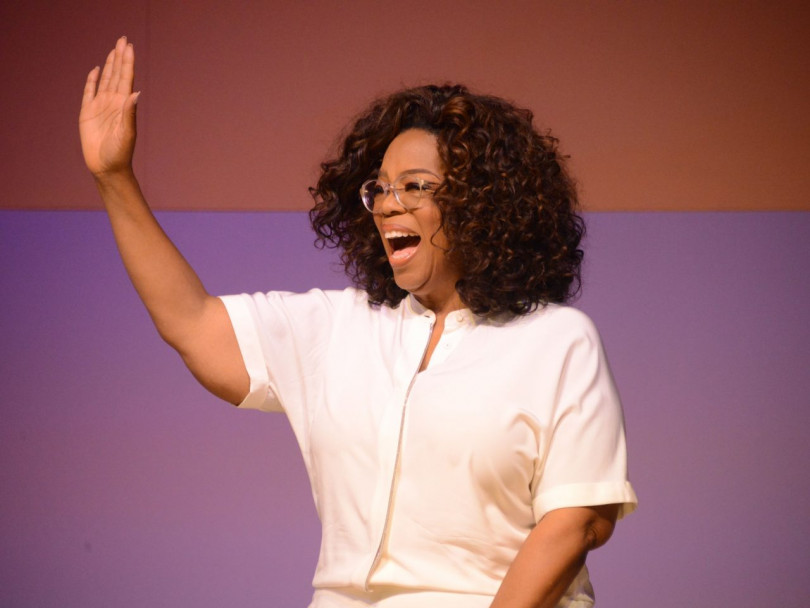 Prince Harry Oprah Winfrey mental health project venture with Apple feature image shows Oprah wearing a white shirt, waving to the audience.