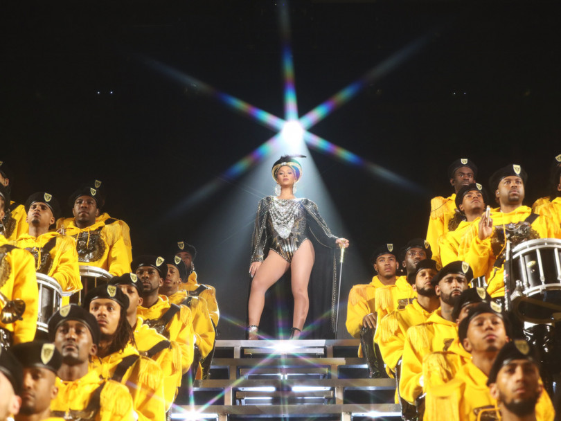 Beyonce stands above men in yellow in Netflix documentary Homecoming