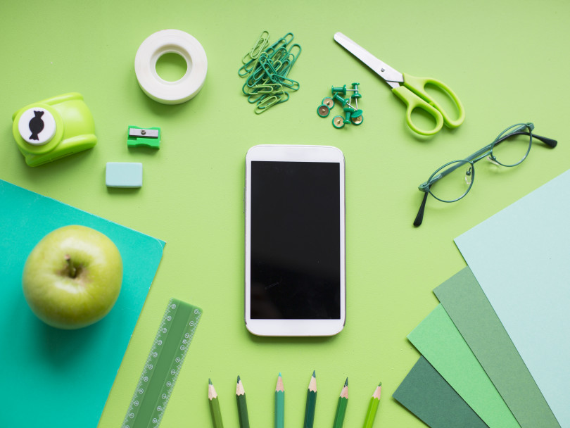 School supplies on green background with phone in centre - eco-friendly apps