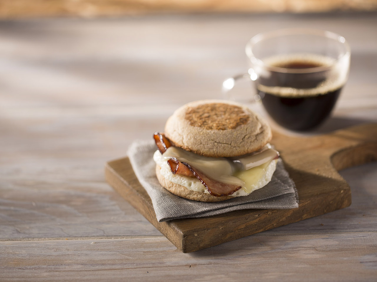 bacon egg breakfast sandwich on cloth napkin, wooden board with coffee — healthiest items to order at starbucks