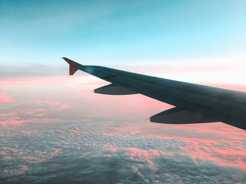 View of airplane wing above sky — how do airplanes affect the environment?