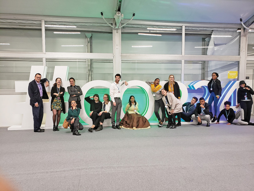 Ana Gonzalez Guerrero and Dominique Souris stand with Youth Climate Lab members in front of #COP24 sign