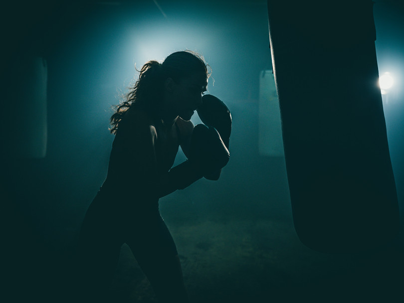 Woman boxes away her suppressed anger in moody lighting