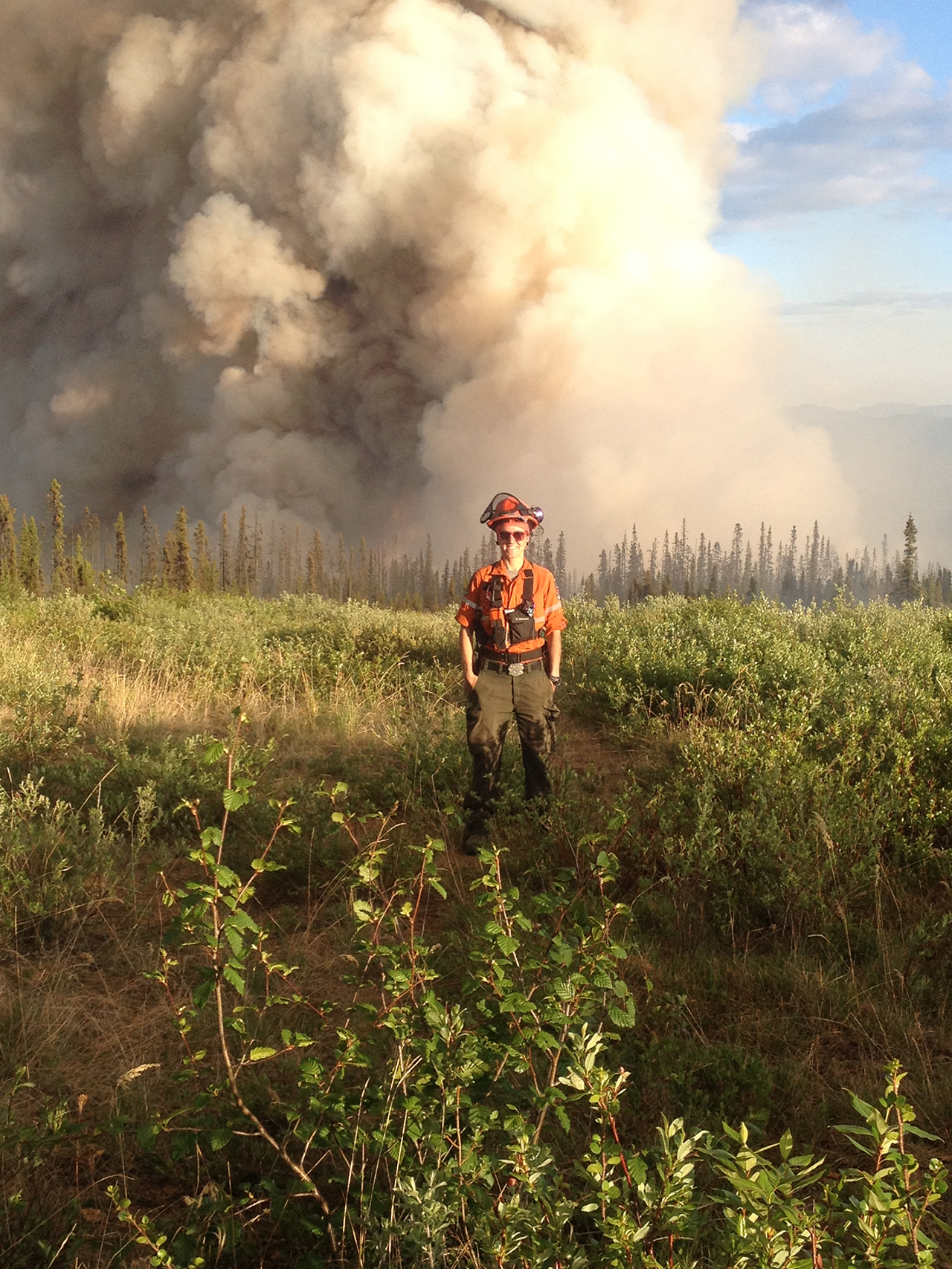 Julie Stankevicius stands in field in firefighting gear as smoke goes up behind her