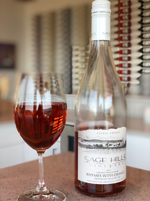 Glass of Sage Hills Rhymes with Orange wine next to its bottle on a counter.