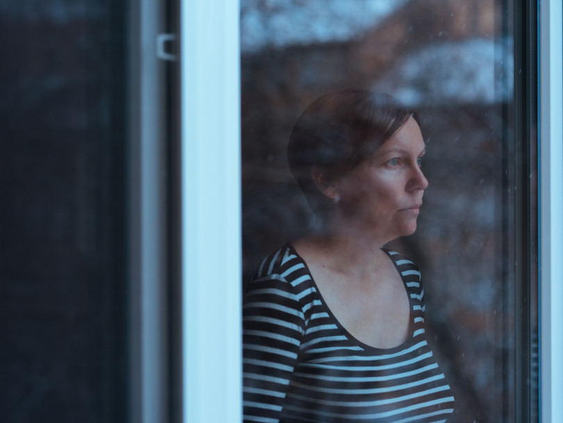 Eco-anxiety stressed and depressed woman standing by the window looking out at rainy weather