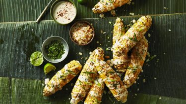 Corn recipes: Overhead shot of A few cobs of Filipino Grilled Corn on a green leafy background