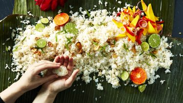 overhead shot of a pile of fried rice on a leafy green background, garnished with garlic, limes, and green onion