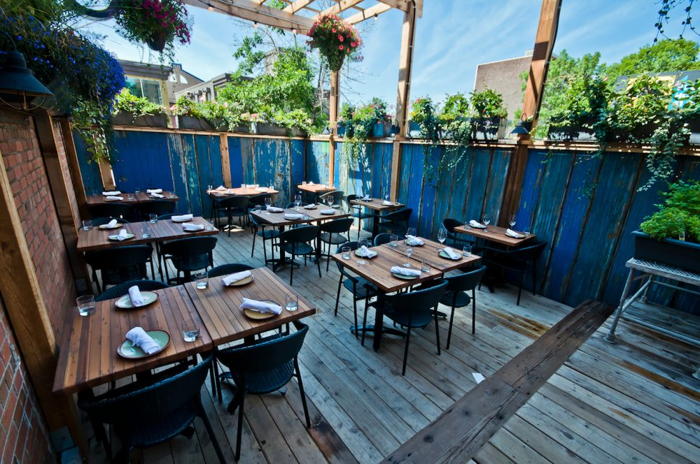 Restaurant patio decor inspiration from Cibo, an image of their patio shows wooden decking, tables and fencing with flower planters along the side and hanging from trellis above