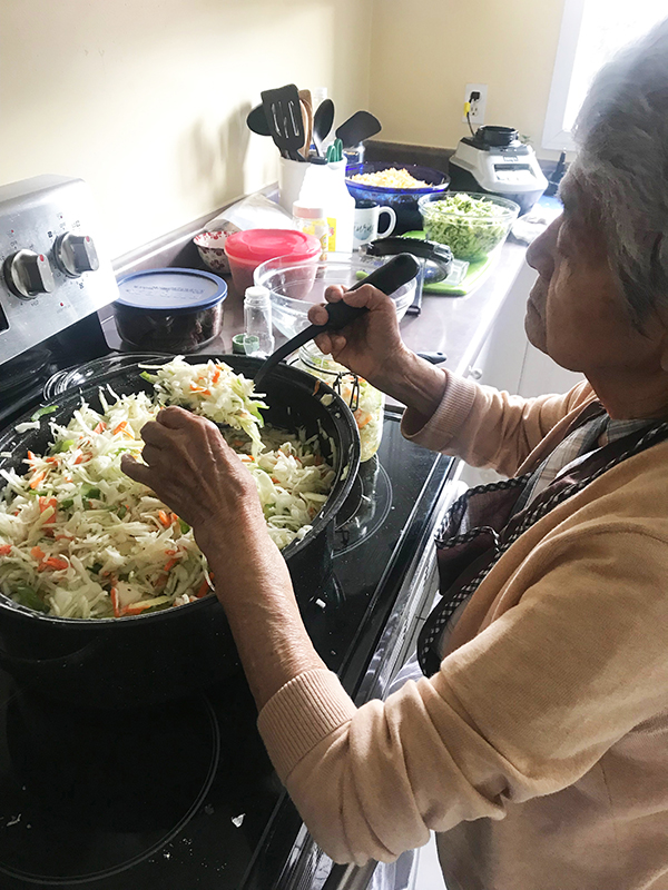cooking pupusas with my grandma: the writer's grandma scooping curtido from a pot on stove