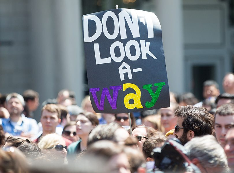 """Photo of a protest focused on a black sign that reads """"don't look a-way""""."""