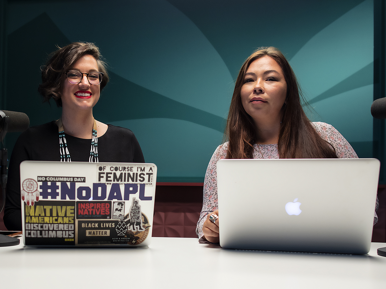 Indigenous podcasts: All My Relations hosts Adrienne Keene with laptop with stickers and Marika Wilbur with Mac laptop