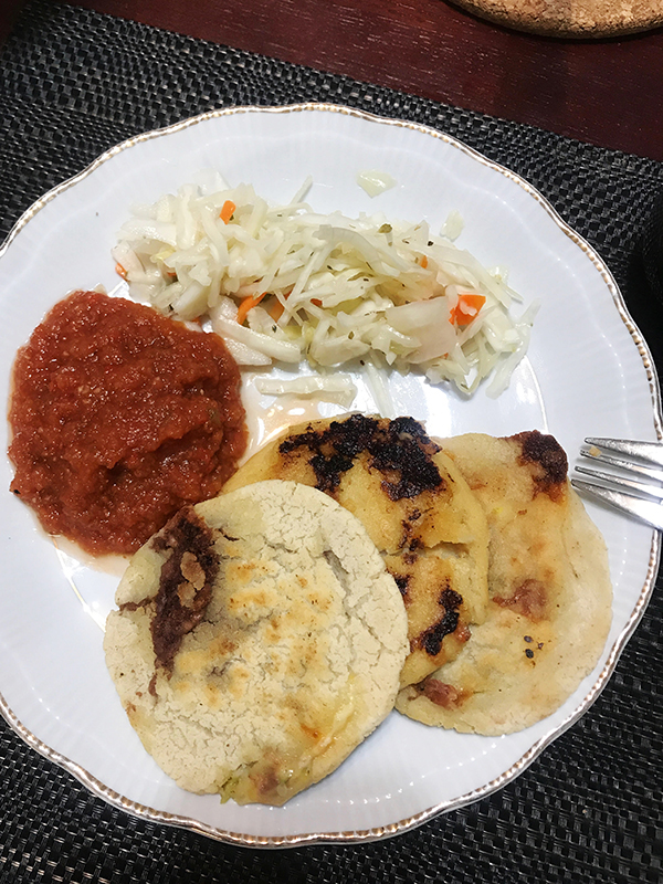 cooking pupusas with my grandma: three pupusas, red sauce, and curtido on plate