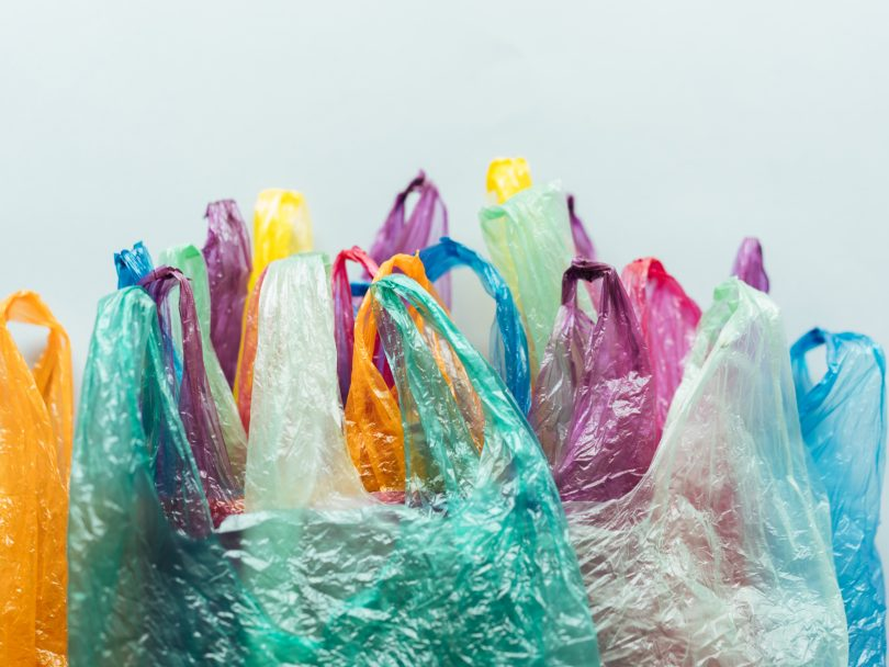 Many multicoloured plastic bags grouped together against a neutral background.