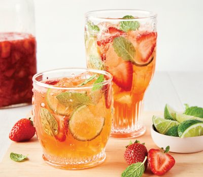 A glass pitcher and short glass sit filled with light orange bubbly liquid with floating strawberries and mint leaves, next to a mason jar filled with mushy-looking strawberries