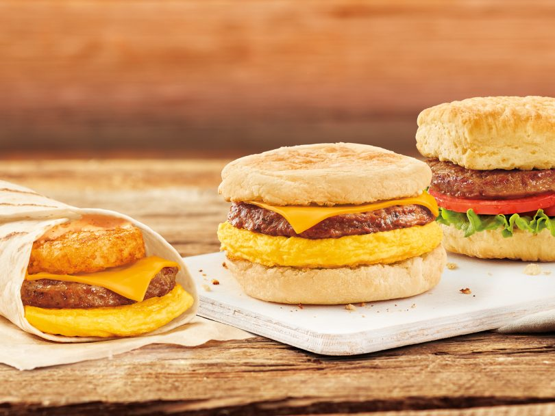 The three new plant-based breakfast sandwiches from Tim Hortons in a line on a wooden table.