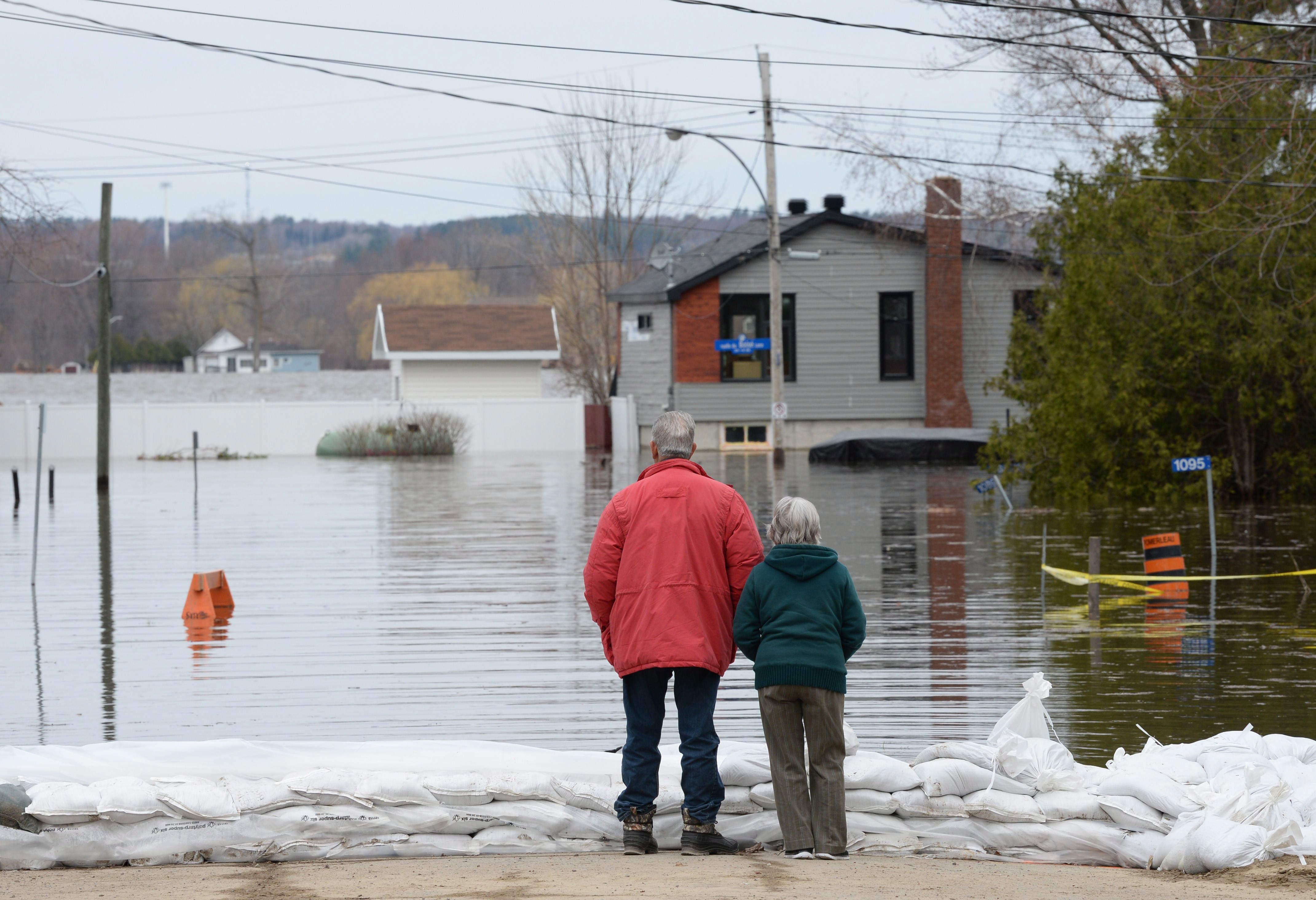 A couple surveys floodwaters from behind a row of sandbags on the street in an east end community of Ottawa.