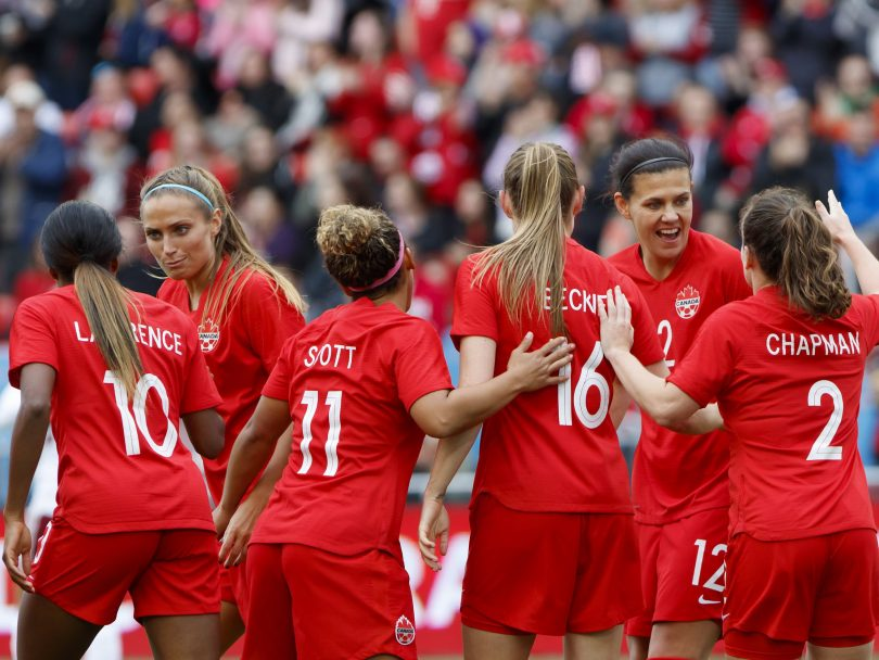 The Canadian Women's Soccer Team during a friendly against Mexico. Six players stand together, congratulating each other.