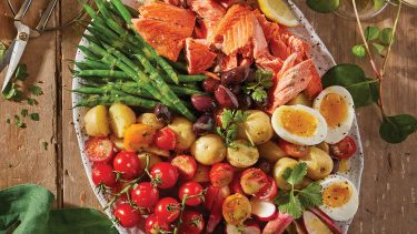Mediterranean diet recipes: Overhead shot of an oval plate filled with tomatoes, green beans, radishes, salmon and soft-boiled eggs on a wooden table.