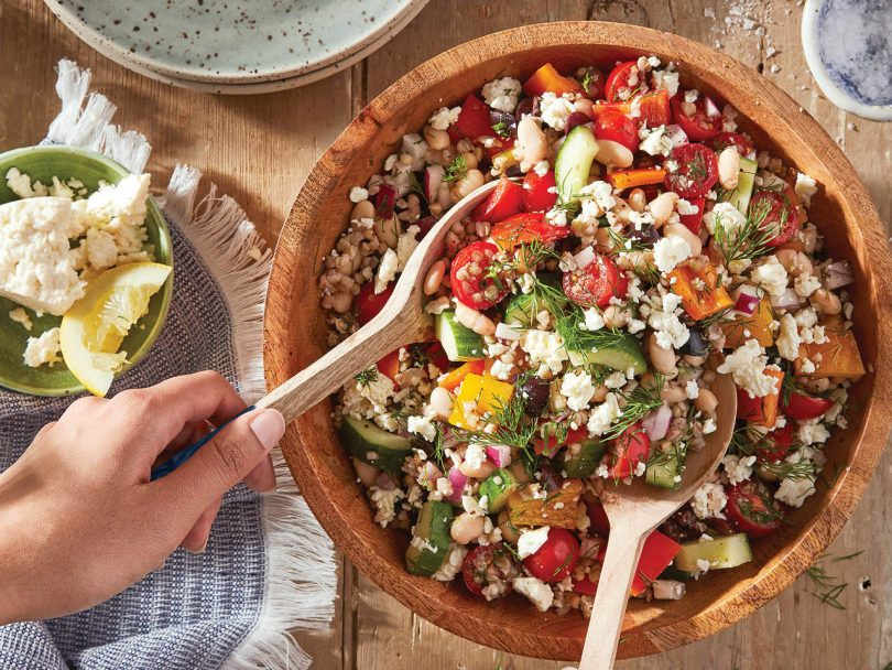 Overhead shot of a wooden bowl filled with Greek Salad with Toasted Buckwheat