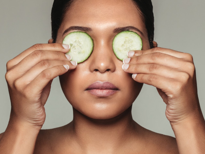 A woman puts cucumbers over her eyes to illustrate a piece on learning to love under-eye dark circles