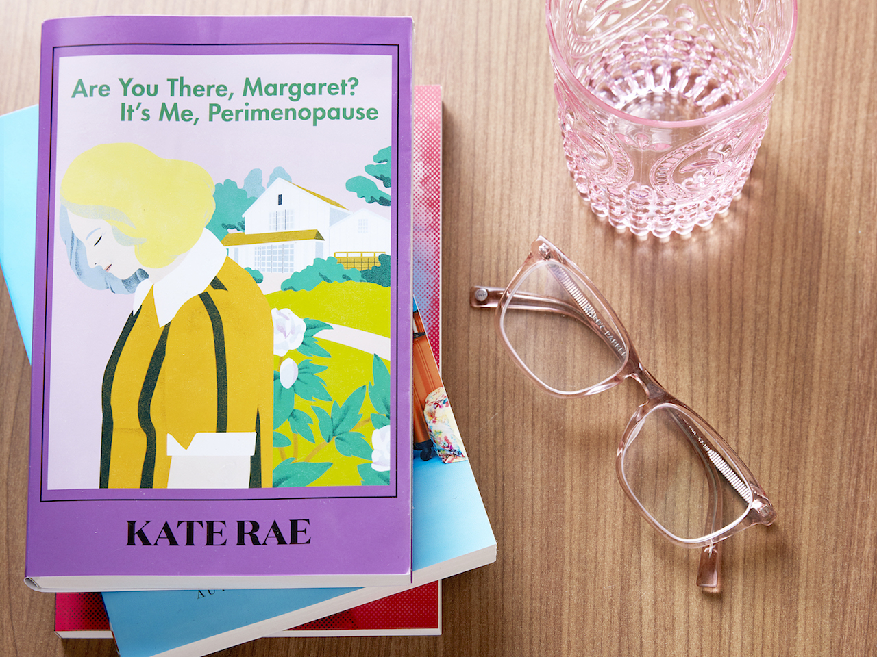 """Overhead shot of a stack of books, glasses, and an empty glass of water. Top book on stack says """"Are you there, Margaret? It's me, Perimenopause"""" and shows a blonde woman hanging her head"""