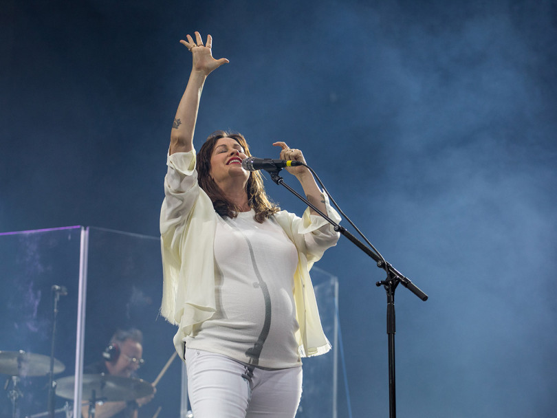 Alanis Morissette Self magazine profile: Alanis in all white performing with one arm raised high and mist rising behind her