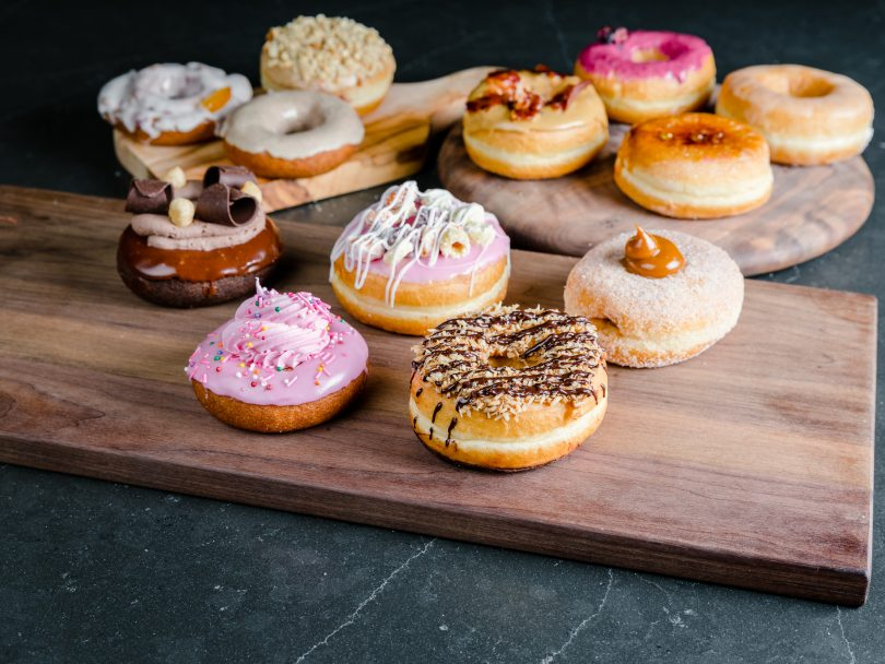 The 12 new Dream Donuts on a wooden platter on a dark countertop.
