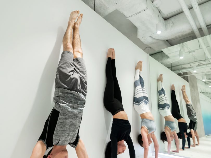 5 people doing handstands against a grey wall in an industrial looking room.