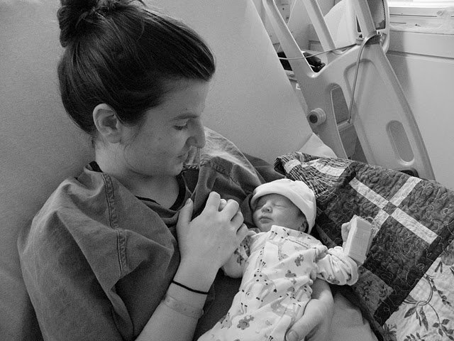 The writer holds her newborn in hospital