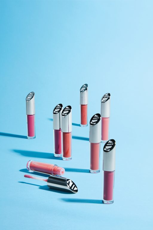 Kjaer Weis lipglosses lined up against a blue background, with one opened and toppled over.