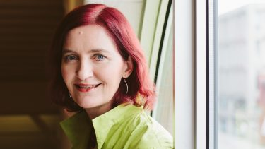 Author of Akin, Emma Donoghue, stands in front of a window wearing a green shirt.