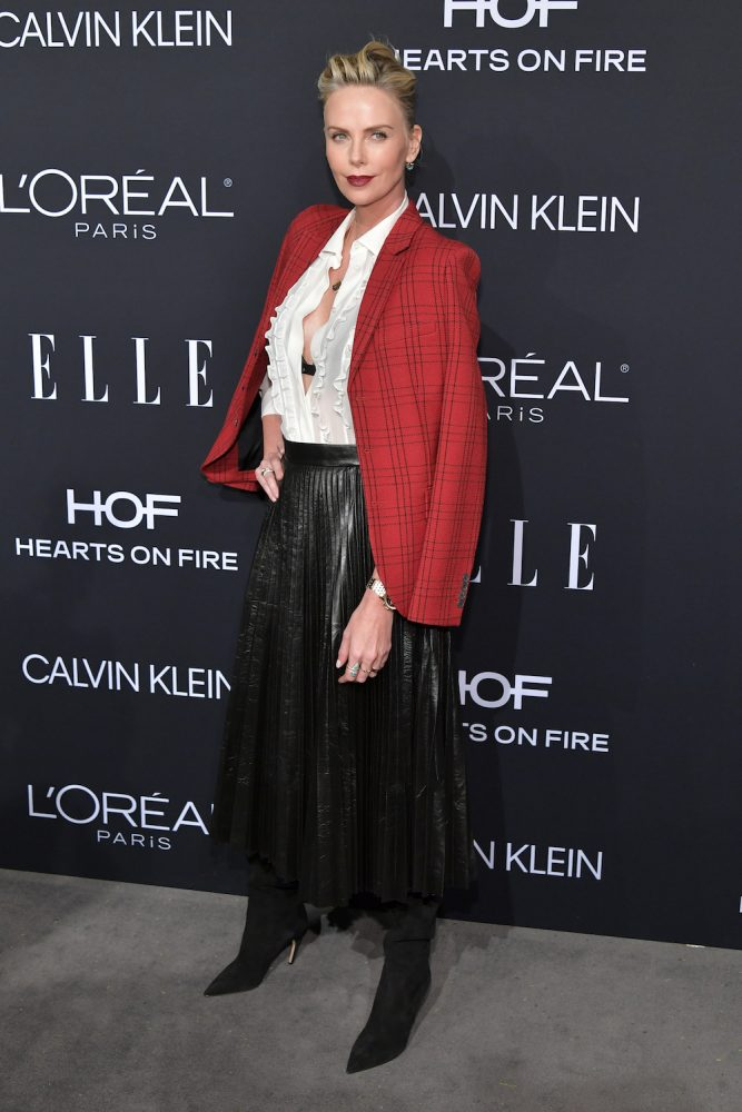 Charlize Theron wearing a midi black skirt, black tall boot heels, red check blazer, and white blouse