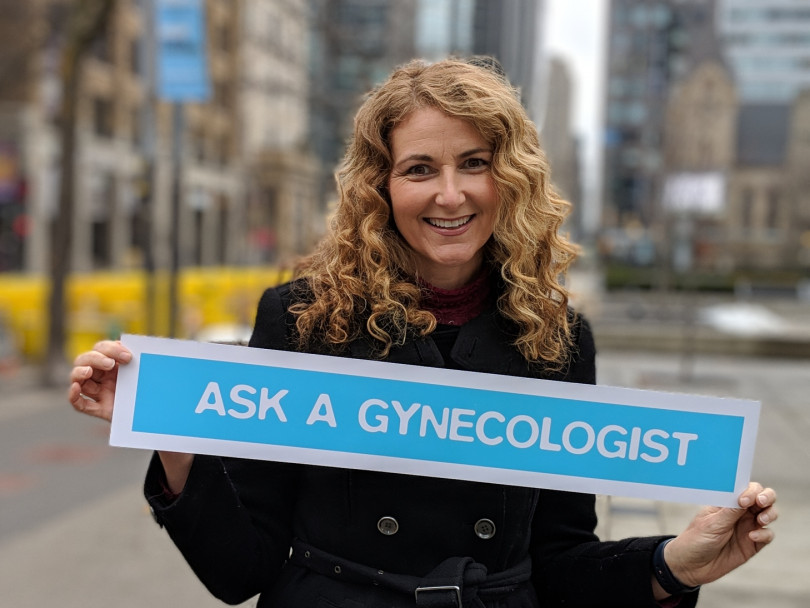 "Dr. Jen Guntler standing outside holding a sign that reads ""Ask a gynaecologist"""