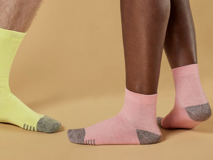 Two pairs of feet wearing pink and yellow pairs of Allbirds' new socks for a product review