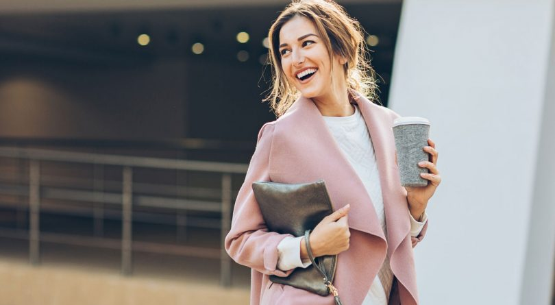 Woman walking, smiling and holding a cup of coffee