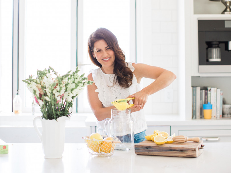 Jillian Harris in her modern kitchen juicing a lemon into a big glass jug.